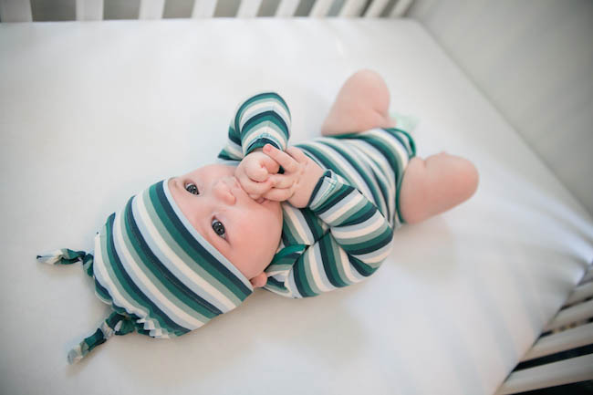 Baby in Crib Green Stripped Onsie